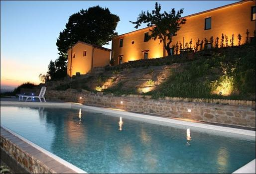 External view of the farmhouse by night with the swimmingpool